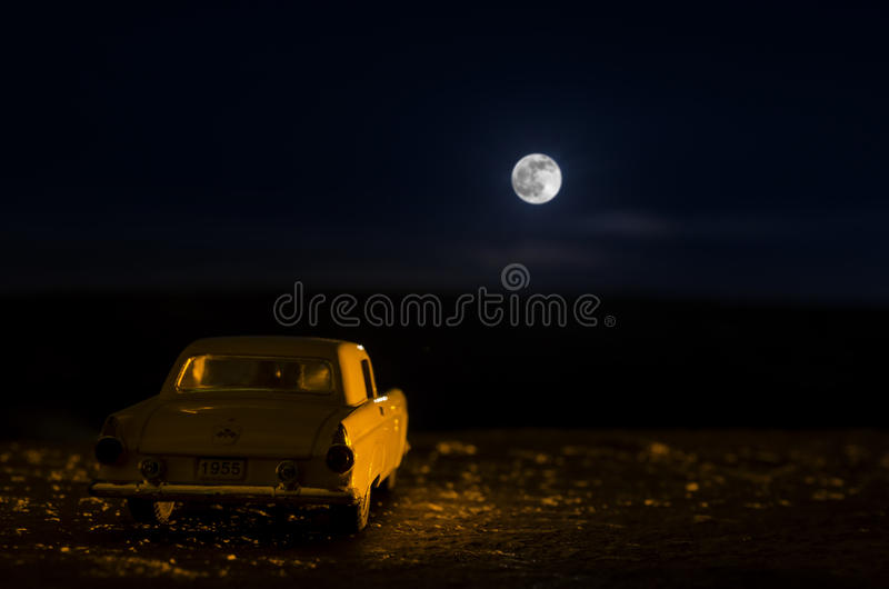 Romantische Szene des alten Weinleseautos mit Paarinnere und des Mondes auf Himmel nachts Silhouettieren Sie Liebe und Auto auf V lizenzfreie stockfotos