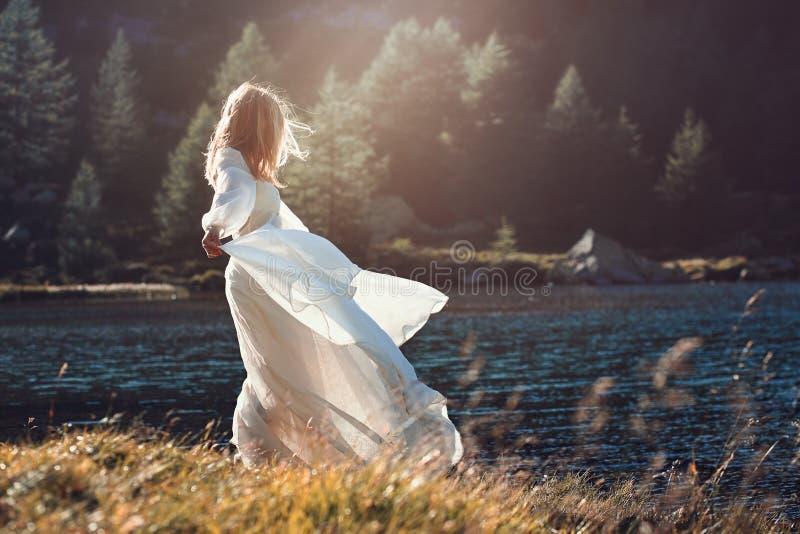 Romantische uitstekende vrouw in zonsonderganglicht stock foto