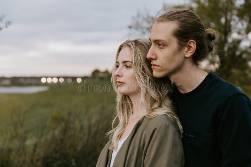Romantische und liebevolle junge erwachsene Paare am Park, der Natur und den Horizont nach Porträt-Bildern betrachtet stockbilder