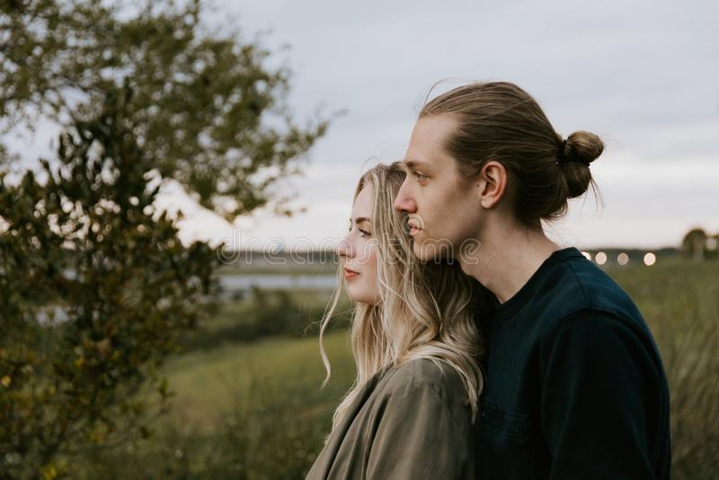 Romantische und liebevolle junge erwachsene Paare am Park, der Natur und den Horizont nach Porträt-Bildern betrachtet lizenzfreies stockbild