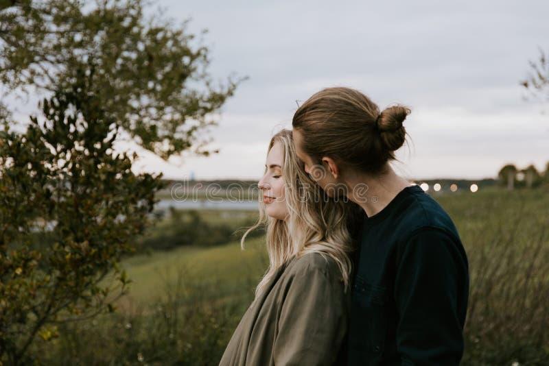 Romantische und liebevolle junge erwachsene Paare am Park, der Natur und den Horizont nach Porträt-Bildern betrachtet stockfotografie