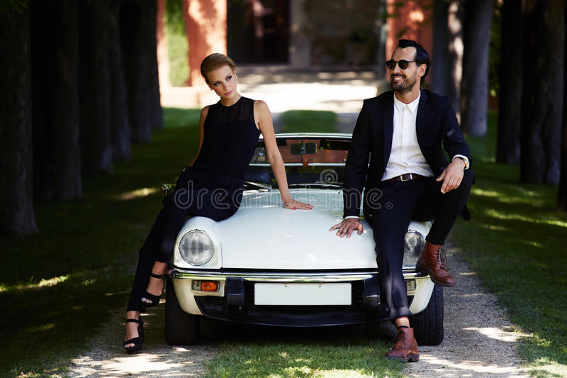 Romantische und moderne Paare, die draußen auf Luxuscabrioletauto im Sommer aufwerfen stockfotos