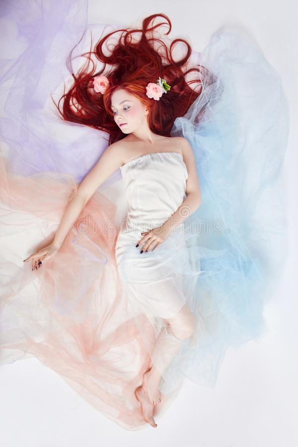 Romantische vrouw met lange haar en wolkenkleding Meisje heldere make-up dromen en perfect lichaam die Roodharigemeisje in lichte royalty-vrije stock foto