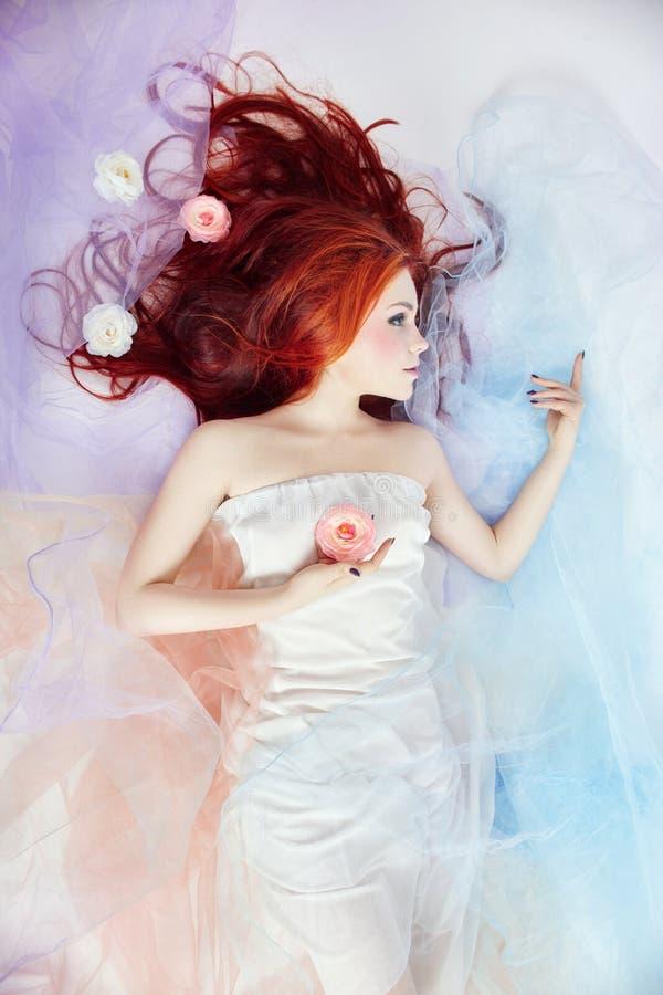 Romantische vrouw met lange haar en wolkenkleding Meisje heldere make-up dromen en perfect lichaam die Roodharigemeisje in lichte stock afbeelding