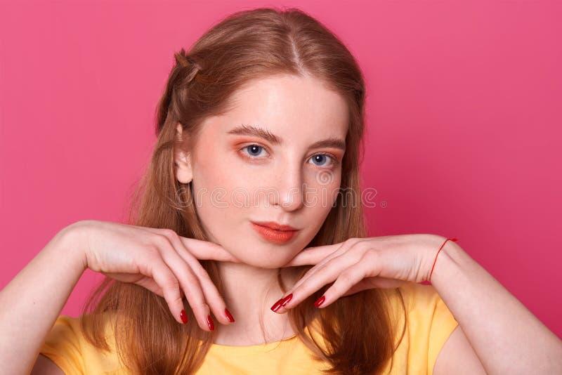 Romantische zarte junge Dame hält Finger mit roter Maniküre nahe nettem frischem Gesicht mit bilden über dunklem rosa Hintergr stockbild