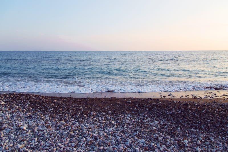 Romantische zonsondergang op de rotsachtige kust royalty-vrije stock foto's