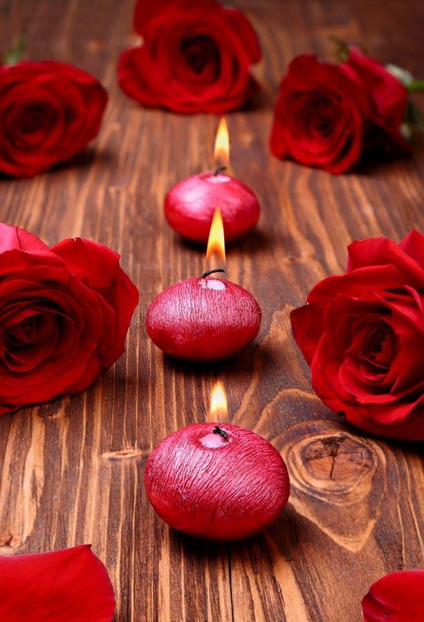 Romantische Zusammensetzung mit roten Kerzen und Rosen lizenzfreies stockfoto
