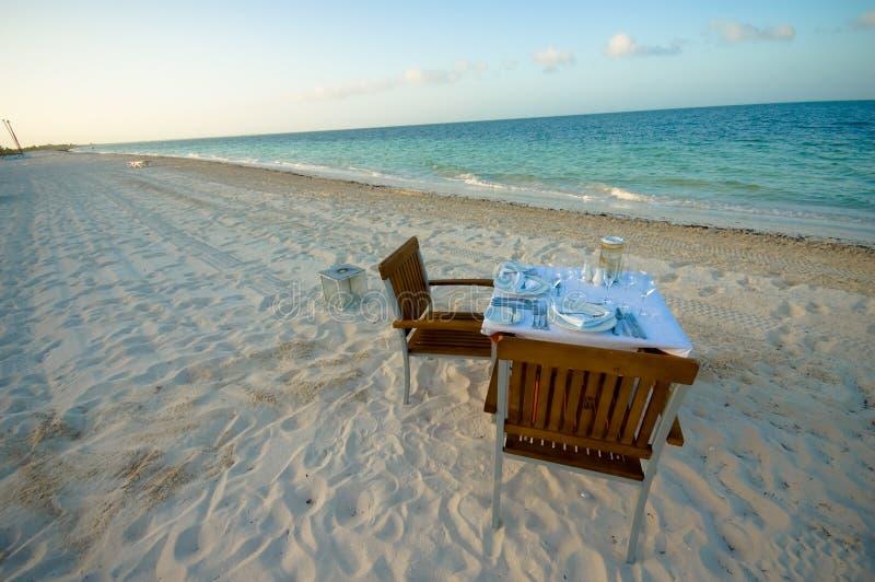 Romantischer Abendtisch auf dem Strand stockbild