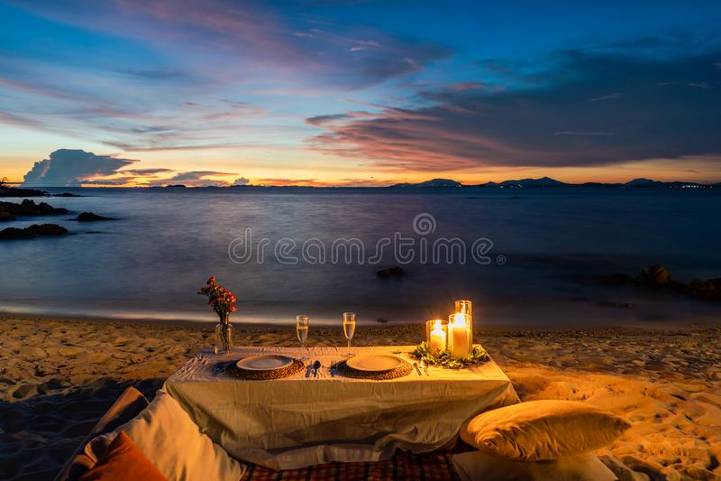 Romantischer Abendtisch eingestellt neben dem Strand in der Sonnenuntergangdämmerungszeit, in Munnok-Insel, Thailand stockfotografie