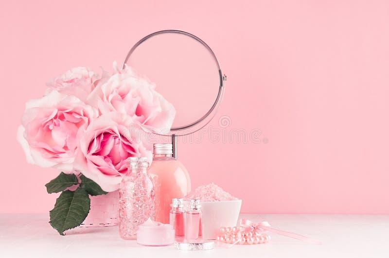 Romantischer Badezimmerinnenraum in der rosa und silbernen Pastellfarbe - Blumen, runder Spiegel, Badzusätze, kosmetische Produkt stockbild