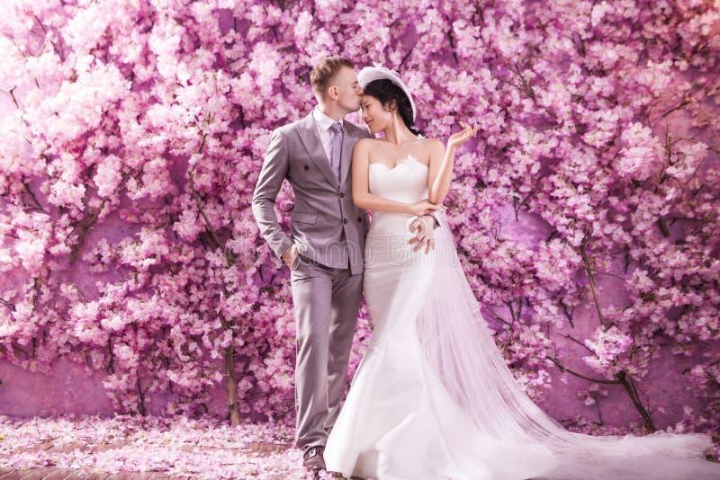 Romantischer Bräutigam, der Braut auf Stirn bei der Stellung gegen die Wand bedeckt mit rosa Blumen küsst stockbilder
