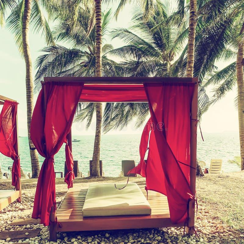 Romantischer Gazeboaufenthaltsraum am tropischen Erholungsort Strandbetten unter Palme lizenzfreie stockbilder