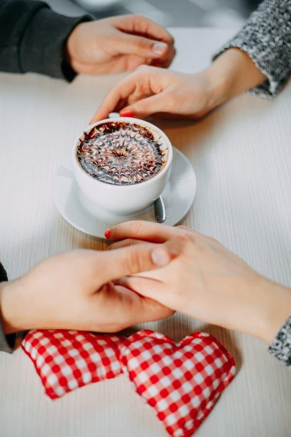 Romantischer Hintergrund, Tasse Kaffee und Hände von Paaren in Liebe O stockfotos