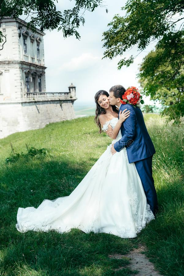 Romantischer Hochzeitsschuß in voller Länge des hübschen Bräutigams, der die gogeous lächelnde Braut in der Backe im Park küsst stockfoto