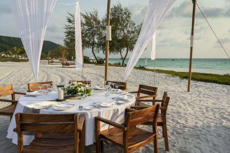 Romantischer Hochzeitstafelentwurf bei Sonnenuntergang draußen auf asiatischem Strand lizenzfreies stockfoto