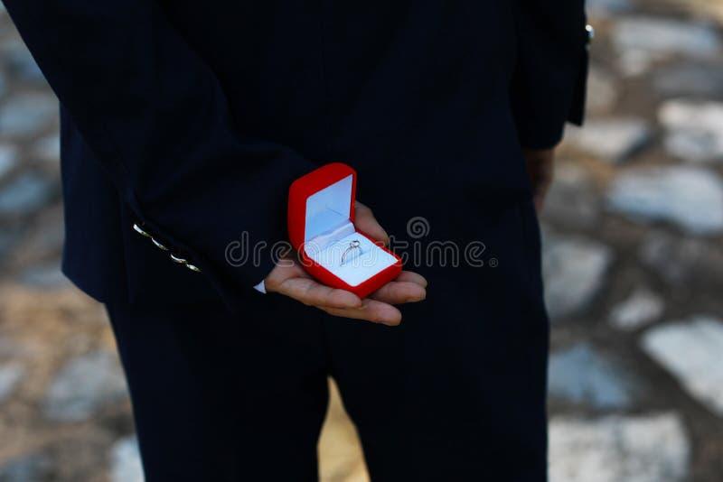 romantischer Mann, der einen Heiratantrag macht Bild des Mannes mit Geschenkbox in der Klage Bild von Paaren mit Ehering und Gesc lizenzfreies stockbild