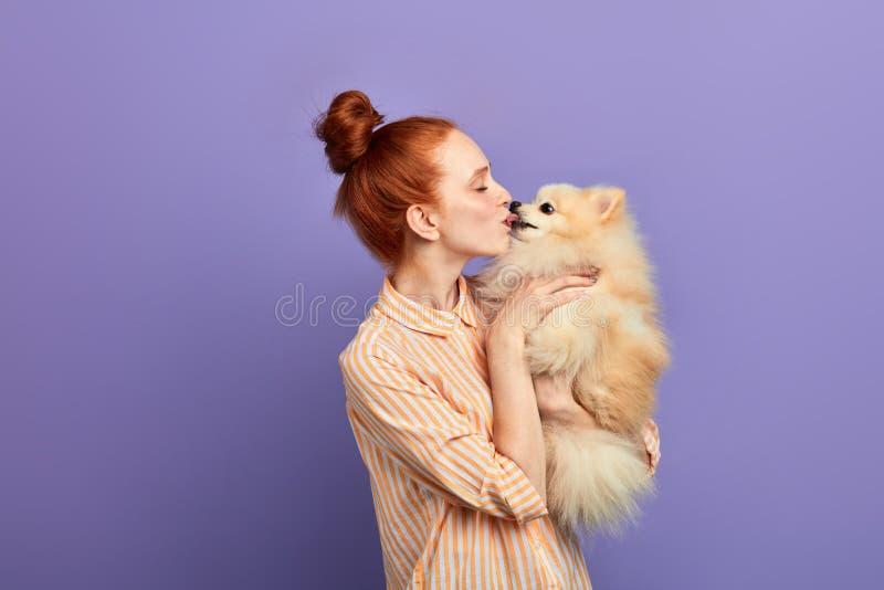 Romantischer Moment, Ingwermädchen, das ihren Hund küsst lizenzfreies stockbild