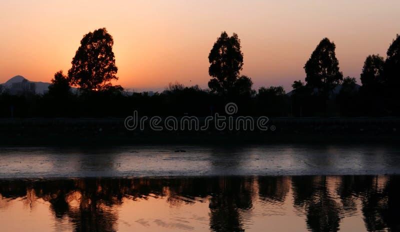 Romantischer orange Sonnenuntergang mit See- und Wasserwellen lizenzfreie stockbilder