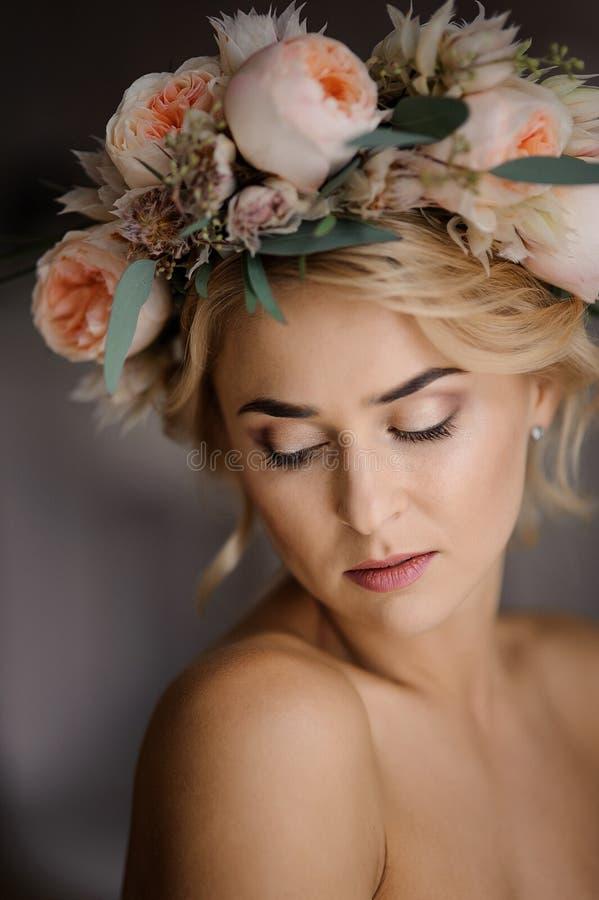 Romantischer schulterfreier Blick von attraktiven Blondinen in einem Blumenkranz mit geschlossenen Augen lizenzfreies stockbild
