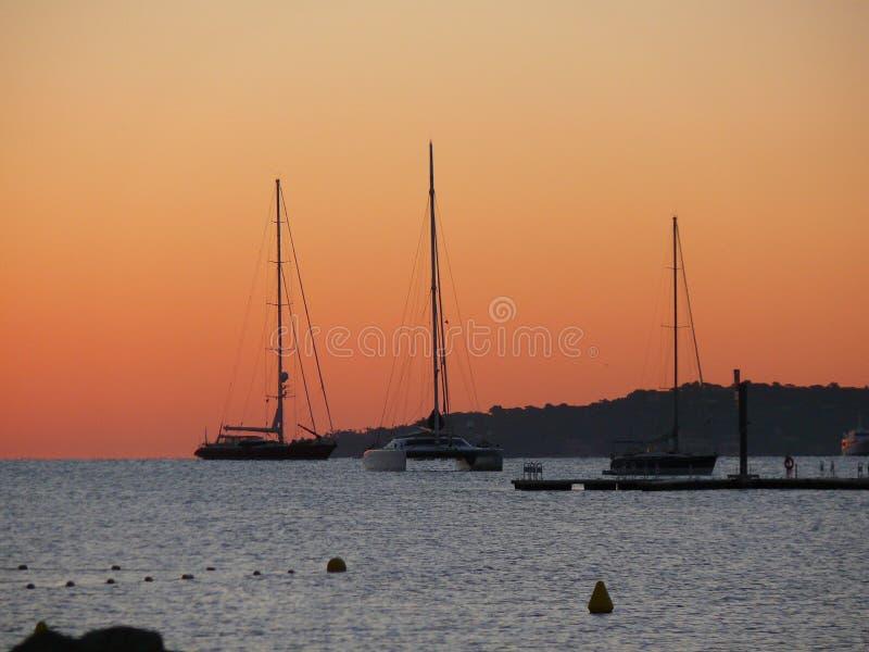 Romantischer Sonnenaufgang auf dem Strand nahe Port-Saint Tropez in Frankreich in Europa Auf dem Meer sind Schiffe und Yachten stockfotos