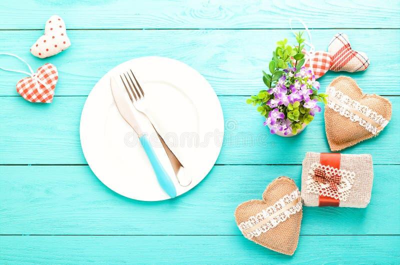 Romantisches Abendessen, Blumen und Herzen auf hölzernem Hintergrund Spott oben stockbilder