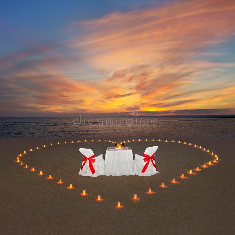 Romantisches Abendessen mit Kerzenherzen am Sonnenuntergangozeanstrand Propos stockfoto