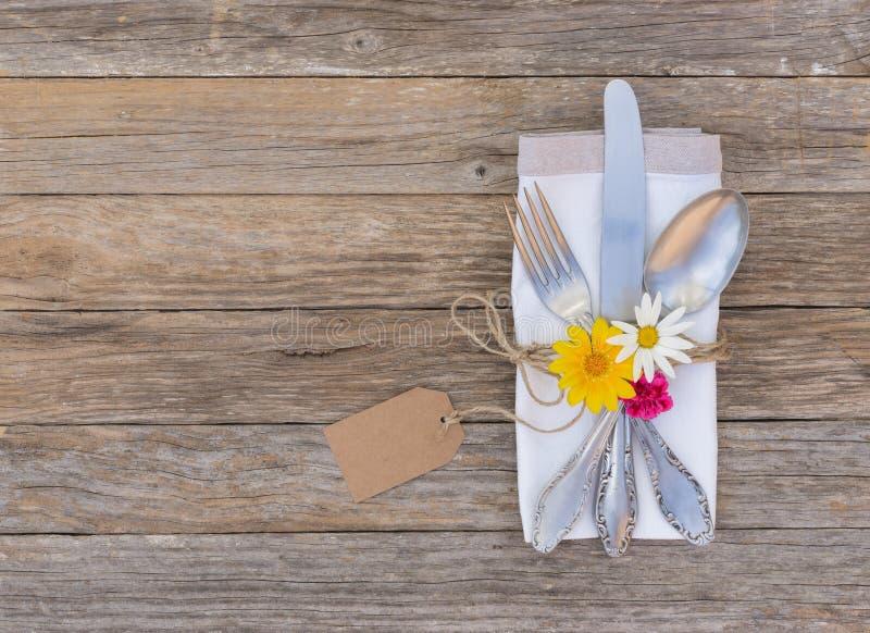 Romantisches Abendessengedeck mit schöner Blumendekoration und leerem Namensschild stockfotografie