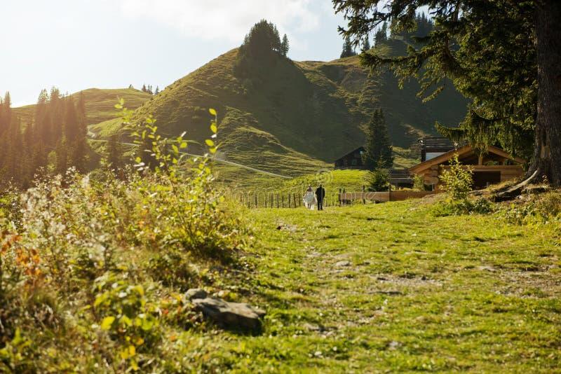 Romantisches Ehepaar, das die Straße vor dem Hintergrund einer wunderschönen Berglandschaft entlang führt lizenzfreie stockfotos