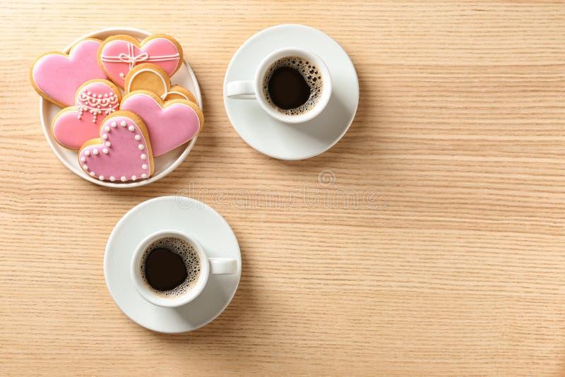 Romantisches Frühstück mit Herzen formte Plätzchen und Tasse Kaffees auf Holztisch, Draufsicht stockbild