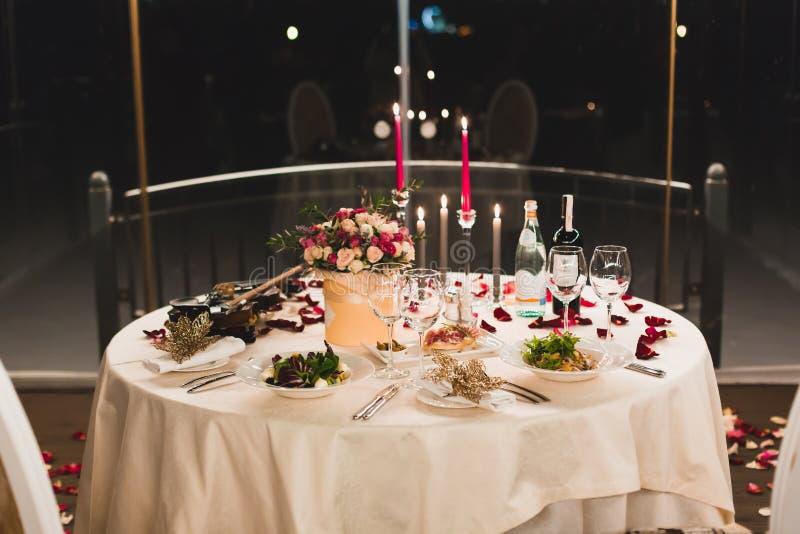 Romantisches Gedeck mit Wein, schöne Blumen im Kasten, leere Gläser, stieg Blumenblätter und Kerzen stockbilder