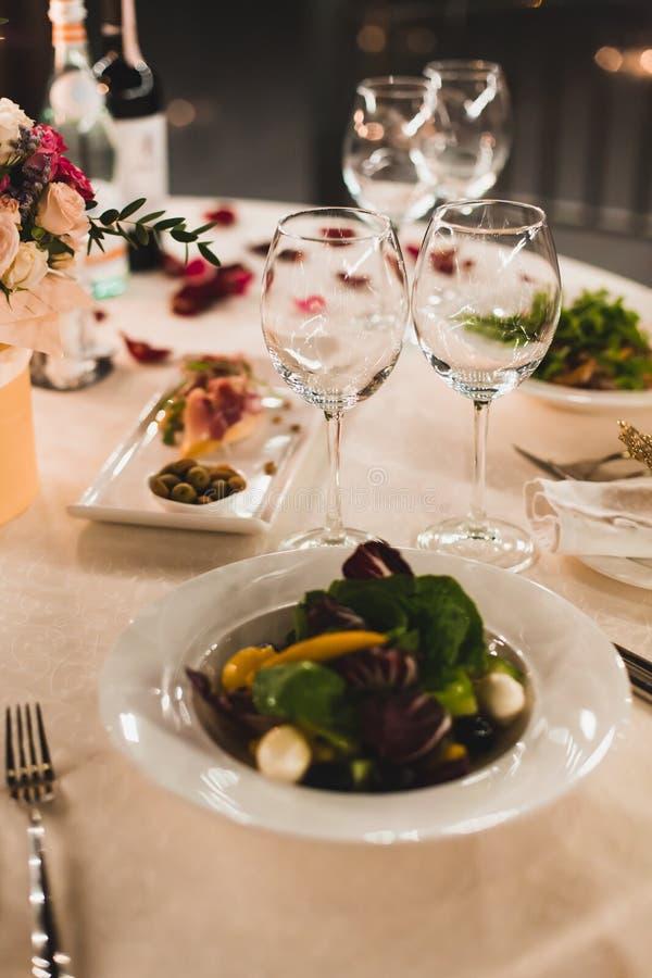 Romantisches Gedeck mit Wein, schöne Blumen im Kasten, leere Gläser, stieg Blumenblätter und Kerzen lizenzfreie stockfotos