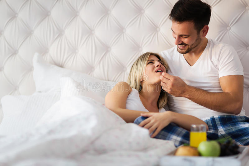 Romantisches glückliches Paar, das im Bett frühstückt stockfoto