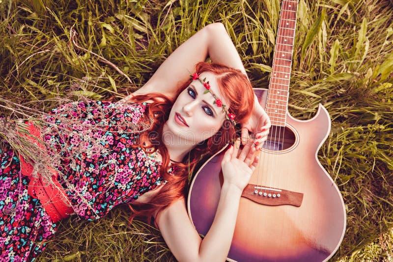 Romantisches Jugendmädchen mit ihrer Gitarre, Sommer, Hippieart stockbild