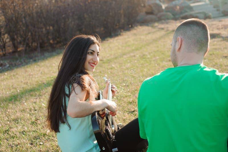 Romantisches junges Paarporträt, das Gitarre unter blauem Himmel spielt lizenzfreie stockfotografie