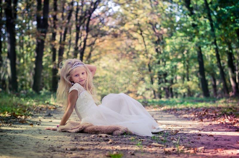 Romantisches Kind, das in Prinzessinkleid unter den Bäumen aufwirft lizenzfreies stockbild