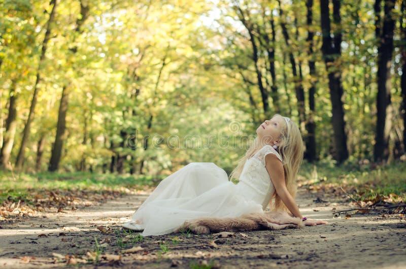 Romantisches Kind, das in Prinzessinkleid unter den Bäumen sitzt stockbilder