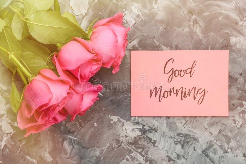 Romantisches Konzept des guten Morgens Ein Blumenstrauß von roten Rosen und von Beschriften, guten Morgen auf einem grauen konkre lizenzfreies stockfoto