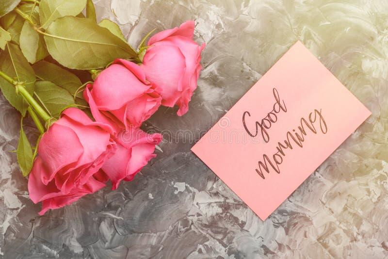 Romantisches Konzept des guten Morgens Rote Rosen und Beschriften, guten Morgen auf einem grauen konkreten Hintergrund wünschend stockfotografie