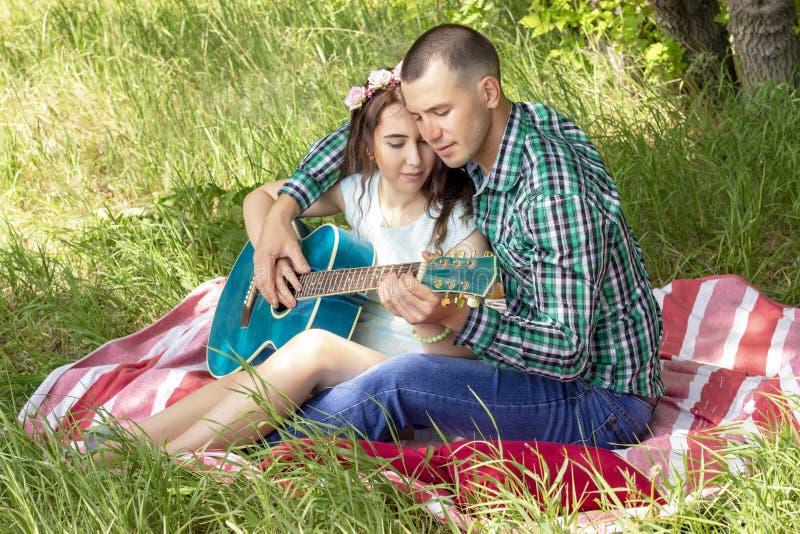 Romantisches Picknick des Sommers Kerl zeigt dem Mädchen, wie man die Gitarre spielt Paare, die auf dem Gras sitzen lizenzfreie stockbilder