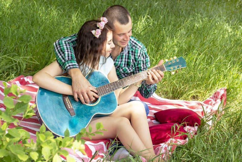 Romantisches Picknick des Sommers Kerl zeigt dem Mädchen, wie man die Gitarre spielt Paare, die auf dem Gras sitzen lizenzfreie stockfotografie