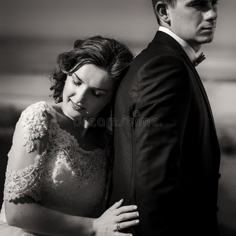 Romantisches Schwarzweiss-Porträt der zarten reizend Braut, die auf der Rückseite ihres hübschen Liebhabers sich lehnt stockfotografie