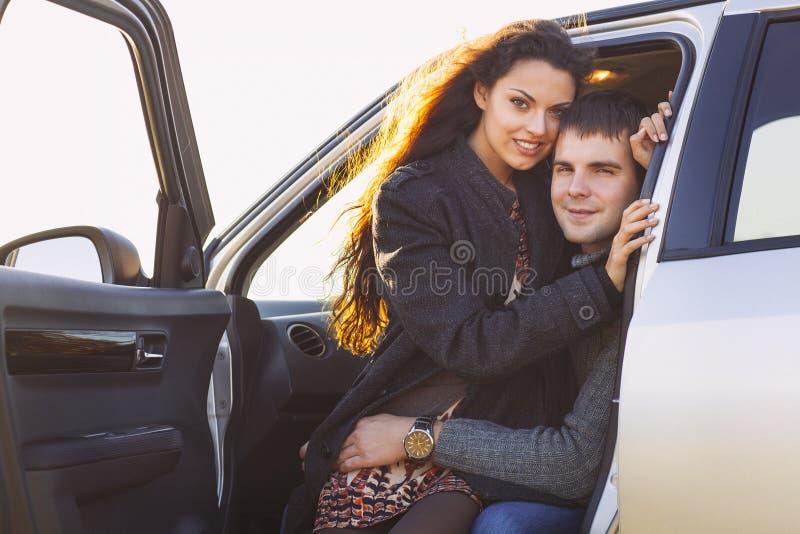 Romantisches Sitzen der Jungelächeln-Paare im Auto stockfotografie