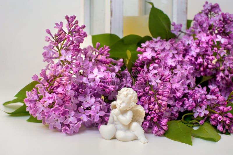 Romantisches Stillleben der lila Blüten- und Engelsskulptur lizenzfreies stockfoto