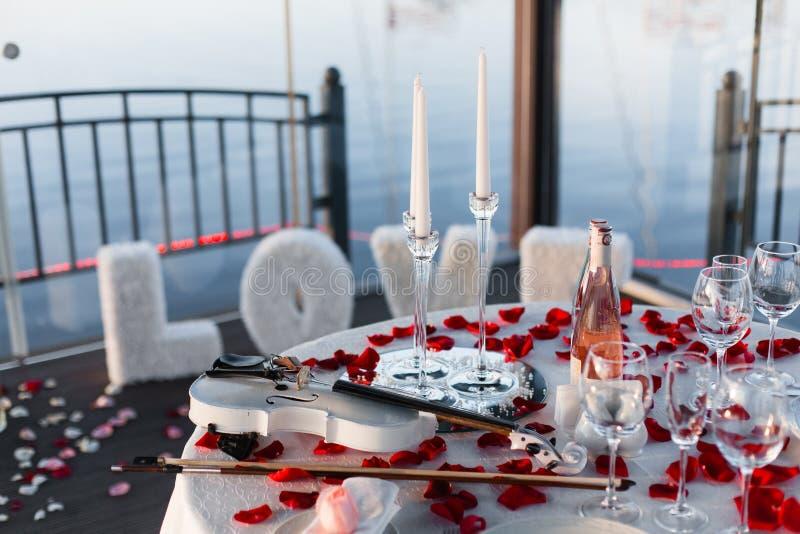 Romantisches Valentinstagabendessen gegründet mit den rosafarbenen Blumenblättern stockfotografie