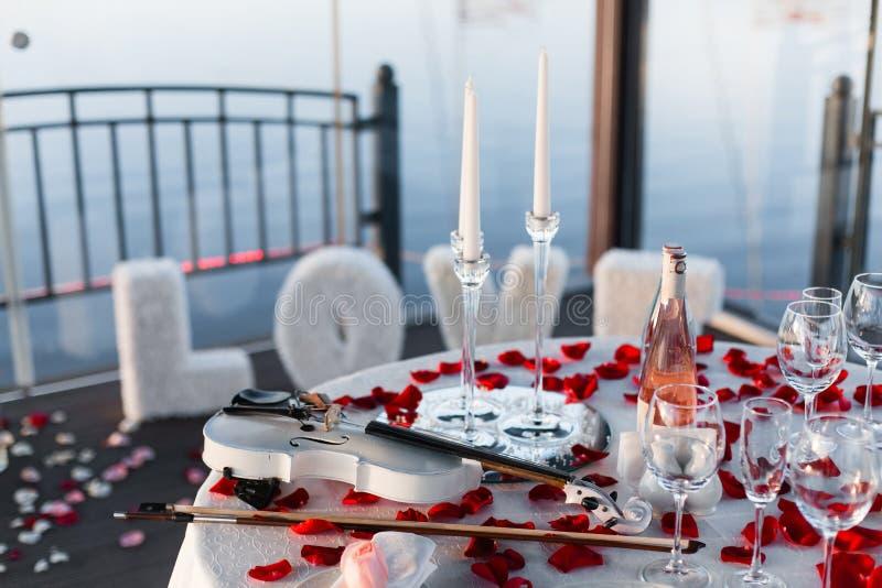 Romantisches Valentinstagabendessen gegründet mit den rosafarbenen Blumenblättern stockbilder