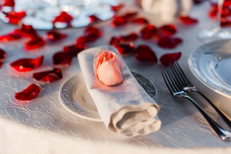 Romantisches Valentinstagabendessen gegründet mit den rosafarbenen Blumenblättern lizenzfreies stockfoto