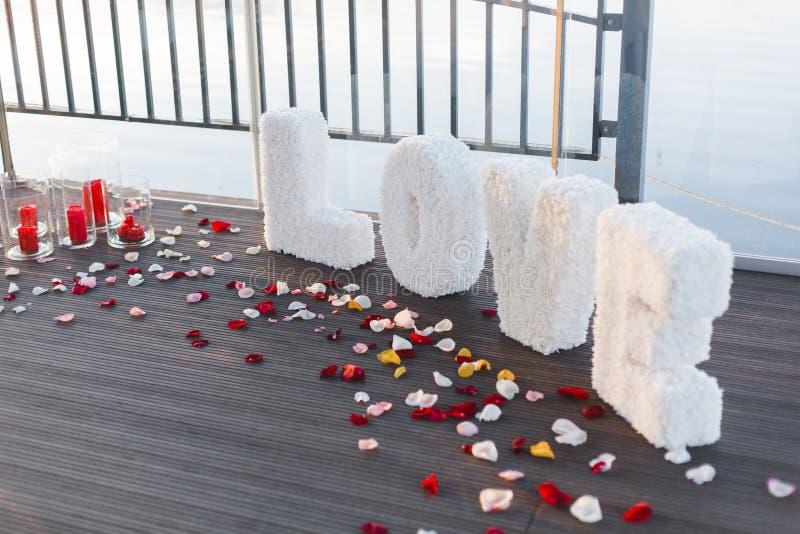 Romantisches Valentinstagabendessen gegründet mit den rosafarbenen Blumenblättern stockbild