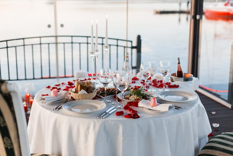 Romantisches Valentinstagabendessen gegründet mit den rosafarbenen Blumenblättern stockfotos