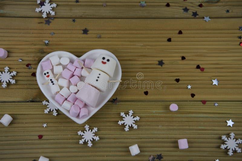 Romantisches Wintersaisonphotographie-Lebensmittelbild mit weißem Teller der Herzform füllte mit Eibischen einiges, das als glück stockbild