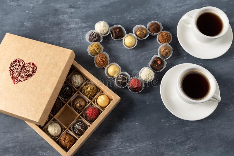 Romantisk atmosfär två koppar kaffe, chokladgodisar och stearinljus lyckliga valentiner för dag kopiera avstånd royaltyfri fotografi